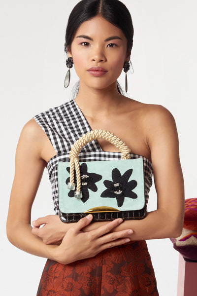 "Thumbnail of model with the Beatrice Purse In Matisse Floral. Your unique statement bag is here in light blue calf suede and chocolate embossed patent leather. This purse features a black embroidered, crystal and beaded floral flap, gold-plated ""arc"" hardware and cream rope top handle"