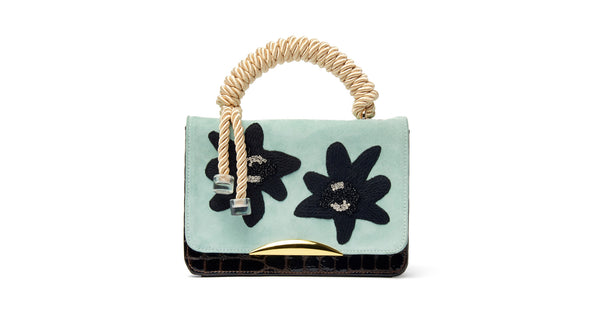 "Full view of Beatrice Purse In Matisse Floral. Your unique statement bag is here in light blue calf suede and chocolate embossed patent leather. This purse features a black embroidered, crystal and beaded floral flap, gold-plated ""arc"" hardware and cream rope top handle"