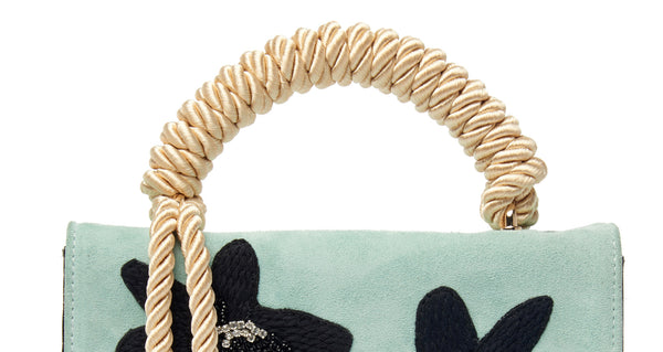 "Top handle detail of Beatrice Purse In Matisse Floral. Your unique statement bag is here in light blue calf suede and chocolate embossed patent leather. This purse features a black embroidered, crystal and beaded floral flap, gold-plated ""arc"" hardware and cream rope top handle"