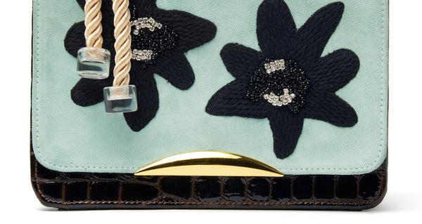 "Bottom detail of Beatrice Purse In Matisse Floral. Your unique statement bag is here in light blue calf suede and chocolate embossed patent leather. This purse features a black embroidered, crystal and beaded floral flap, gold-plated ""arc"" hardware and cream rope top handle"