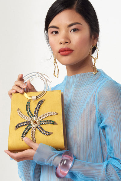 Thumbnail of model with Pronto Purse in Crystal Flower. We love absolutely every sumptuous detail of this mini statement bag, from the mustard satin and nude saffiano leather to the hand-embroidered sequin and crystals, to the clear acrylic round top handles. This one is a must-have.