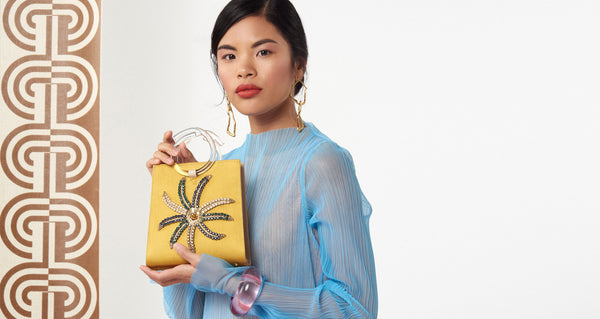 Model with the Pronto Purse in Crystal Flower. We love absolutely every sumptuous detail of this mini statement bag, from the mustard satin and nude saffiano leather to the hand-embroidered sequin and crystals, to the clear acrylic round top handles. This one is a must-have.