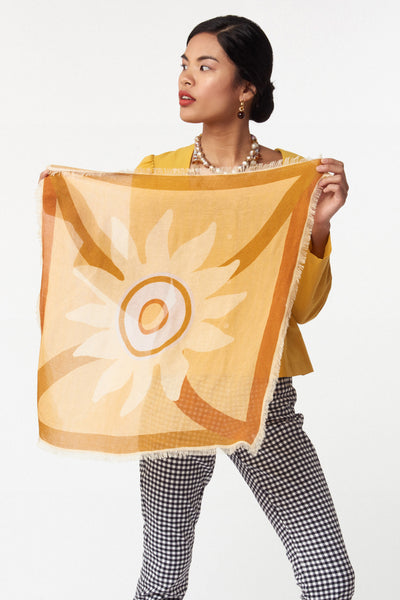 Thumbnail of model holding Neck Scarf in Bohemian Sun. Our square wool neck scarf  will keep you cozy and  comes with unique gold-plated kidney closure for maximum styling opportunities. Light tangerine with pale yellow and periwinkle graphic sunshine print and fringed edges.