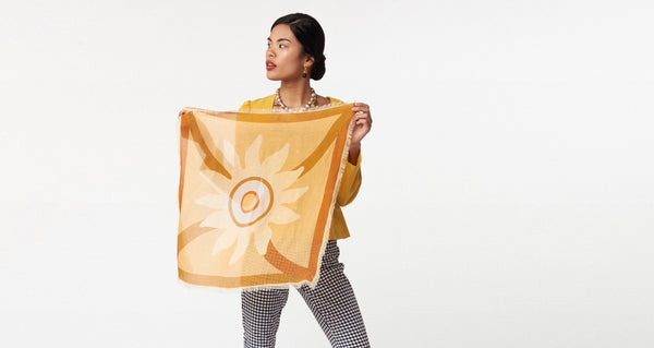 Model holding the Neck Scarf in Bohemian Sun. Our square wool neck scarf  will keep you cozy and  comes with unique gold-plated kidney closure for maximum styling opportunities. Light tangerine with pale yellow and periwinkle graphic sunshine print and fringed edges.