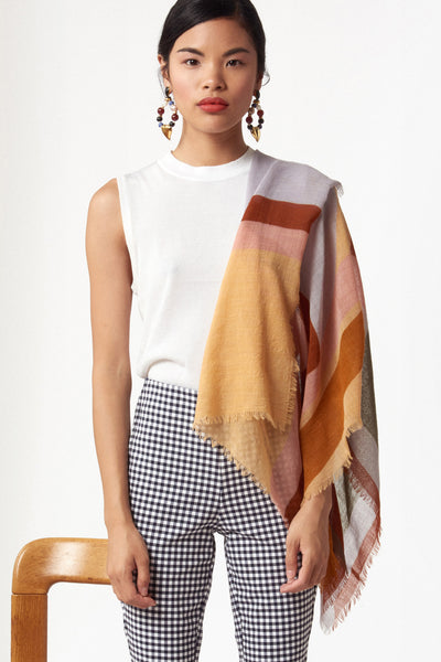 Thumbnail of model wearing the Large Graphic Stella Scarf. Our oversized rectangular 100% wool scarf will keep you cozy and can be styled in so many ways. With statement-making peach, periwinkle, rust and olive multicolor graphic print and fringed edges.