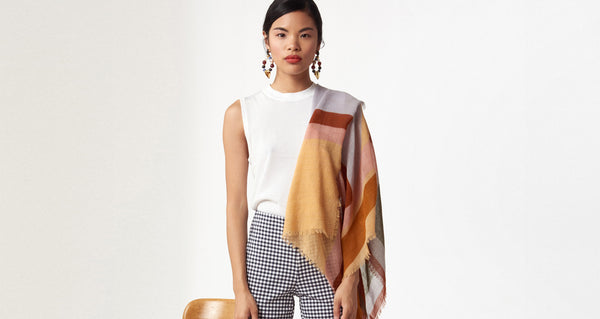 Model wearing the Large Graphic Stella Scarf draped over her shoulder. Our oversized rectangular 100% wool scarf will keep you cozy and can be styled in so many ways. With statement-making peach, periwinkle, rust and olive multicolor graphic print and fringed edges.