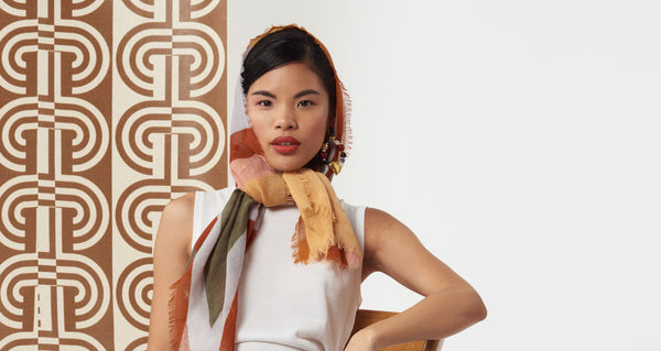 Model wearing the Large Graphic Stella Scarf on her head. Our oversized rectangular 100% wool scarf will keep you cozy and can be styled in so many ways. With statement-making peach, periwinkle, rust and olive multicolor graphic print and fringed edges.