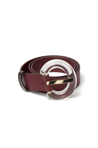 "Thumbnail of Sofia Belt In Burgundy. A fresh take on a classic staple. Adjustable wide burgundy leather belt with oversized clear acrylic ""arc"" buckle."