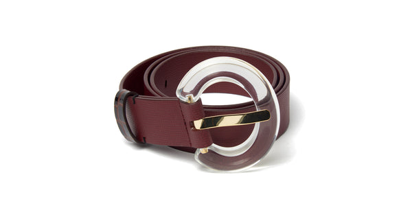 "Full view of Sofia Belt In Burgundy. A fresh take on a classic staple. Adjustable wide burgundy leather belt with oversized clear acrylic ""arc"" buckle."