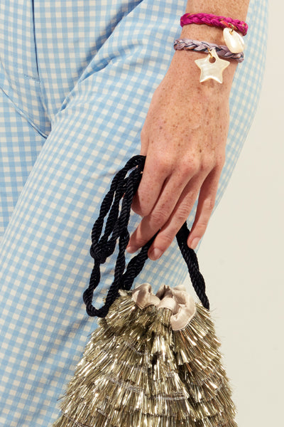 Thumbnail of model wearing the Lavender Field Bracelet. Wear it to the beach, give it to your best friend, layer it up all season long and into the next. The light purple hand-braided bracelet is an easy wardrobe win that you won't want to take off. With large pearl star charm and freshwater pearl and tassel closure.