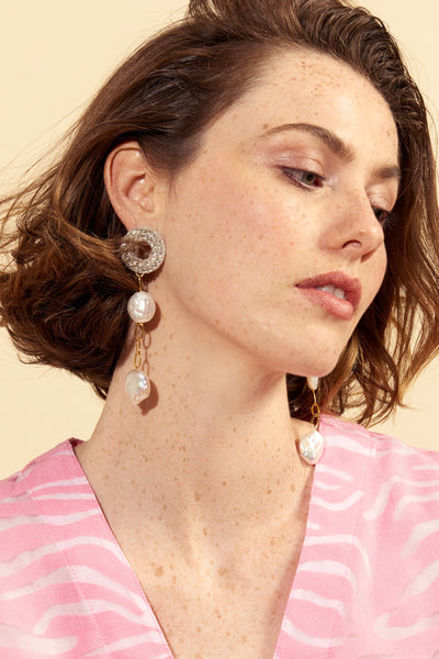 Thumbnail of model wearing the Chateau Pearl Earrings. Stop them cold in their tracks in our supremely elegant gold vermeil chain column earrings, perfect for holiday parties and fireside hangs alike. With silver hand-embroidered sequin discs and freshwater pearls.