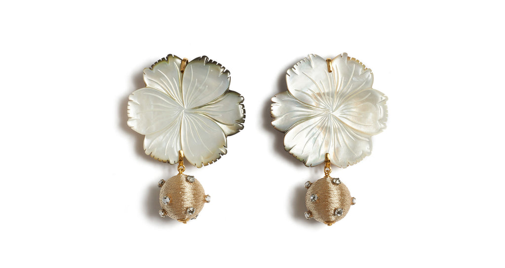 Full view of Pearl Blossom Earrings. Organic meets opulent. Wear the best of both worlds in our artistic carved mother-of-pearl flower earrings, punctuated by gold silk cord beads studded with tiny glass details.
