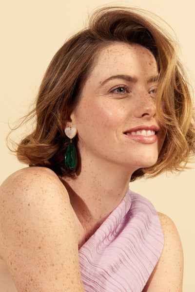 Thumbnail of model wearing the Roumana Earrings. Cue the drama in gold-plated statement earrings with sweet mother-of-pearl heart tops and rich green malachite teardrops. We'll be wearing this versatile pair with black velvet, silk camis and chunky knits.