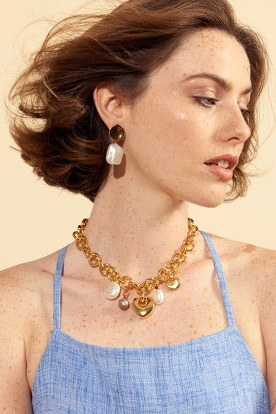 Thumbnail of model wearing the Pearly White Earrings. Show off the goods in our abstract gold-plated brass earrings with hanging, square-shaped freshwater pearls. These are set to be an elegant and timeless addition to your jewelry box.