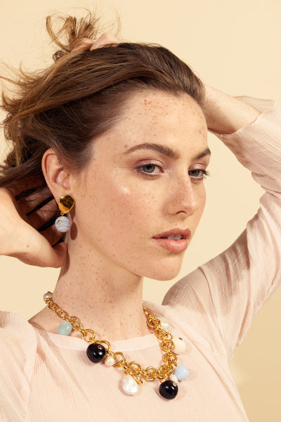 Thumbnail of model wearing the Lalla Earrings. We la la love these lightweight gold-plated petal top earrings for everyday wear.  Featuring cool blue lace agate hanging beads set with faceted semiprecious blue topaz. Make it a match with our Lalla Necklace.