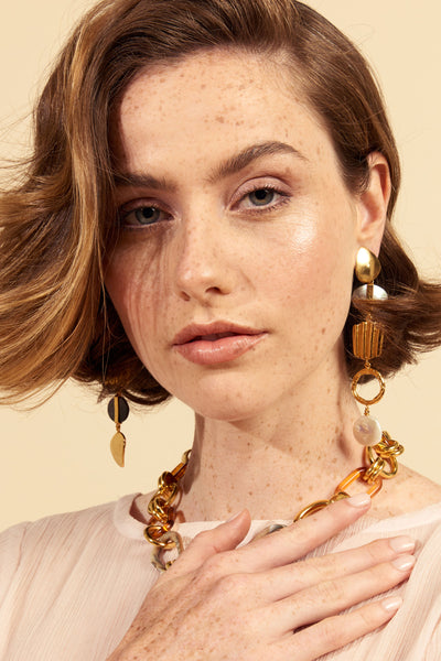 Thumbnail of model wearing the Treasure Hunt Earrings. Search no more, your textured, shimme...