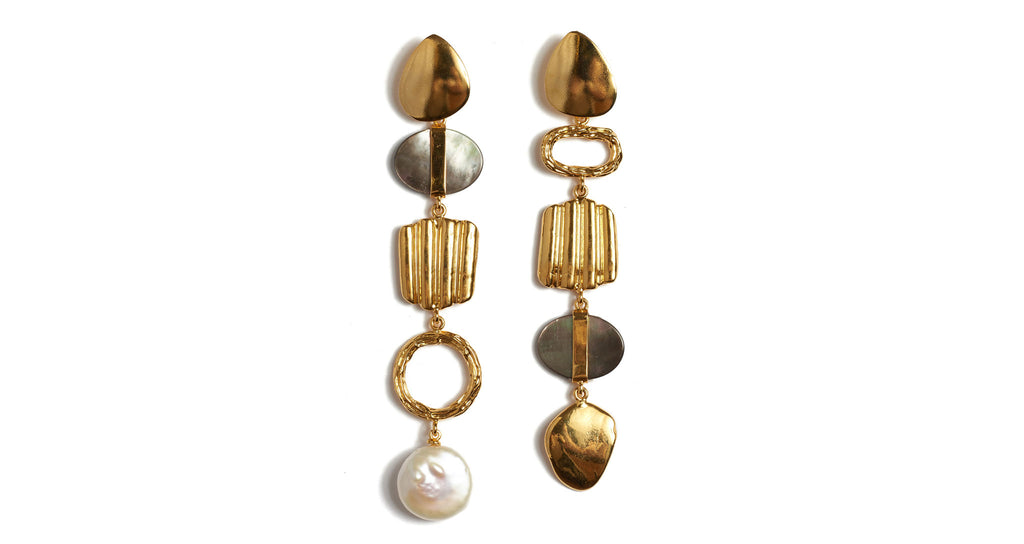 Full view of Treasure Hunt Earrings. Search no more, your textured, shimmery, and versatile pair of chic statement earrings is here. These asymmetrical gold-plated columns are studded with a unique trove of linked abstract shapes, black lip mother-of-pearl, and hanging freshwater pearl.
