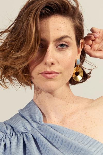 Thumbnail of model wearing the Promenade Hour Earrings. Going somewhere? Telegraph some true satellite chic in our gold-plated disc earrings with blue angelite stone tops and textured gold link detail.