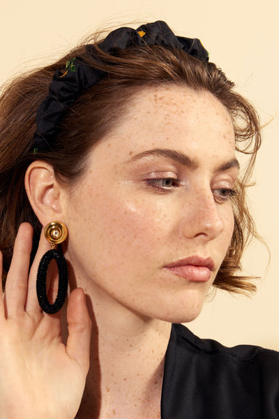 "Thumbnail of model wearing the Allure Earrings. Go for full glamor in this poised pair of ebony beaded earrings with gold ""nautilus"" tops and inset crystal detail. They're the perfect accessory for office parties and black-tie events alike."