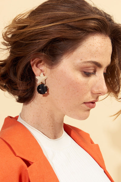 Thumbnail of model wearing the Starburst Earrings. Don't settle for the dark side of the room-- you'll be a stand-out in these small but mighty sparklers.  Black silk cord beads studded with tiny glass details are suspended by mother-of-pearl stars in this heavenly pair of earrings.
