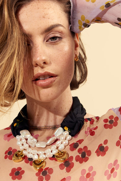 Thumbnail of model wearing the Tangerina Necklace. Freshen up your look in our sweetly dramatic freshwater pearl statement necklace. With daisy bud print silk shantung and hanging gold-plated heart charms, this mixed media marvel will be a lively wake-up call for your wardrobe.