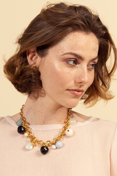 Thumbnail of model wearing the Lalla Necklace. Get the party started in this sweet confection of a chunky chain necklace. In gold-plated brass with a delightful assortment of freshwater pearls, blue lace agate, aquamarine and acrylic charms set with semiprecoius faceted stones. For more style candy, pair with our complementary Lalla earrings.