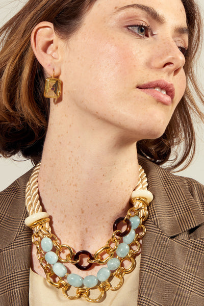 Thumbnail of model wearing the Marbella Necklace. Inspired by its namesake coastal town in Spain, the Marbella necklace embodies natural beauty, upscale charm, and mixed media craftsmanship. In cream-colored twist rope with a multi-strand gold-plated chain, aquamarine nuggets, tortoise-colored acrylic rings, and freshwater pearl.