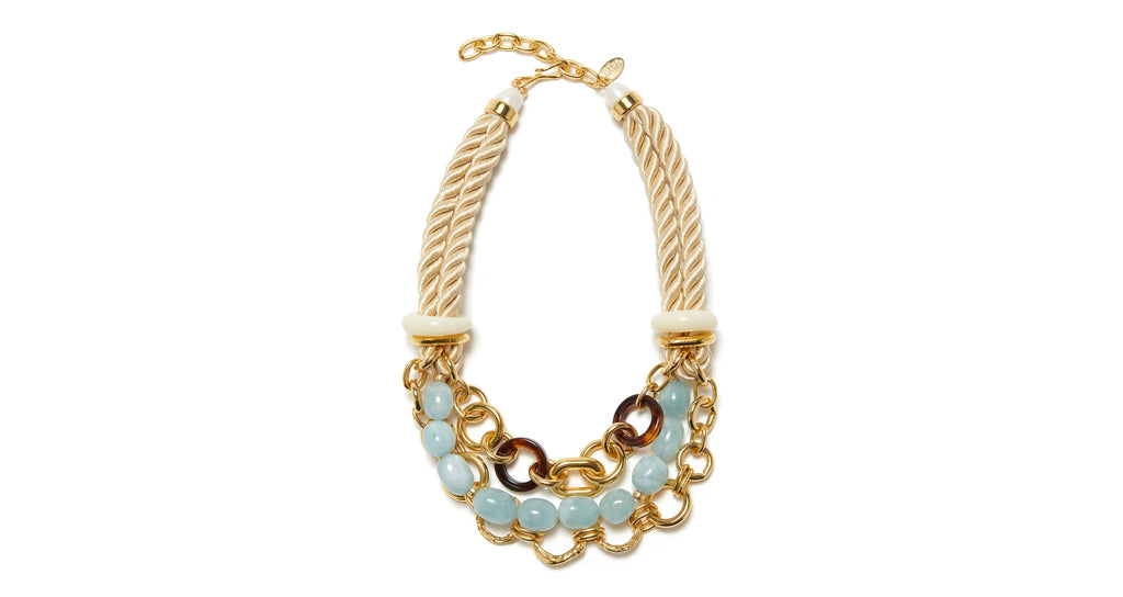 Full view of Marbella Necklace. Inspired by its namesake coastal town in Spain, the Marbella necklace embodies natural beauty, upscale charm, and mixed media craftsmanship. In cream-colored twist rope with a multi-strand gold-plated chain, aquamarine nuggets, tortoise-colored acrylic rings, and freshwater pearl.