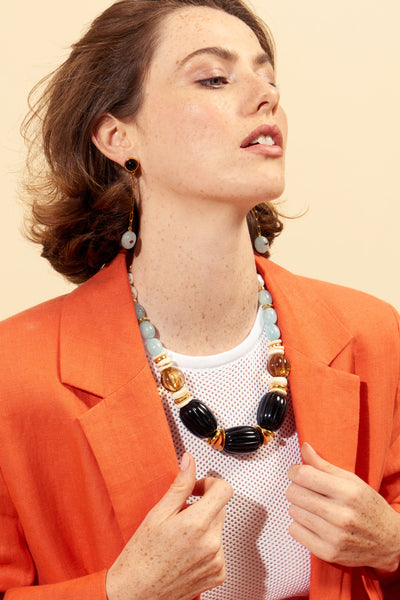 Thumbnail of model wearing the Villa Necklace. Plan your next getaway in the Villa, our single-strand necklace that will be equally at home in a luxurious sea-side town or on the big city streets. This easy-to-wear statement piece features beads of freshwater pearl, aquamarine nugget, shell, gold-plate, and fluted amber and black acrylic.