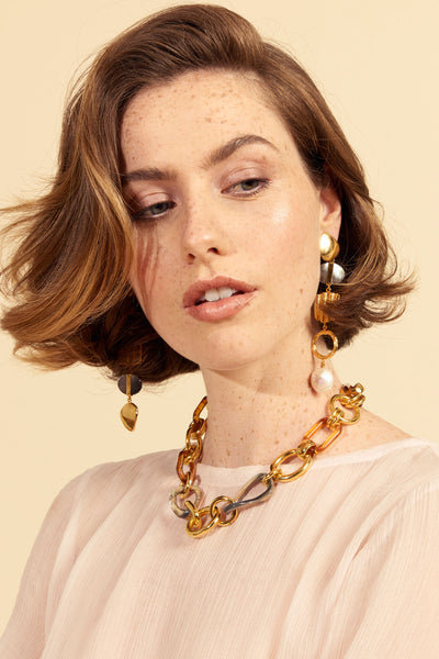 Thumbnail of model wearing the Abalone Link Necklace. Attention: your prep classic chain-link necklace has joined forces with arty mixed materials for a truly unique accessory vibe. There are no weak links in this look, a deft combination of gold-plated brass, tortoise-coloured acrylic, and abalone shell.
