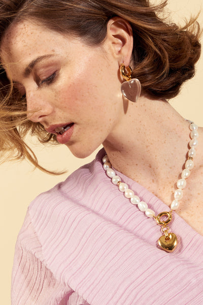 Thumbnail of model wearing the Heartbreak Necklace. The heart motif is perennially beloved around here, and we think this iteration is pretty perfect. We've paired a classic pearl single-strand necklace with gold-plated heart pendant for a look you'll love for years to come.