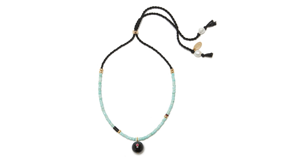 Full view of Orbit Necklace. You need some space. Get an out-of-this-world look that loves to layer with our turquoise heishi bead necklace. With a black agate bead set with semiprecious rhodolite and an adjustable black hand-twisted cord back.