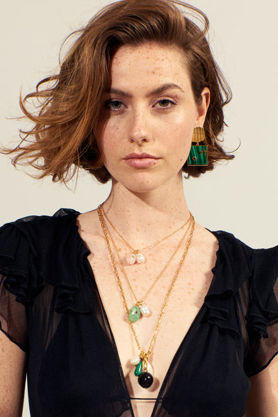 Thumbnail of model wearing the Cypress Charm Necklace. Elevate a cozy sweater or amp up a low-cut blouse with the gold vermeil chain necklace featuring a bevy of organic-shaped charms made from freshwater pearls, malachite, green opal and acrylic with faceted semiprecious stone. Give your neck some layering love and wear it with the Green Oasis Necklace.
