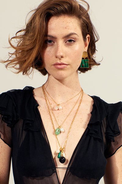 Thumbnail of model wearing the Green Oasis Necklace. Let simplicity be your style salvation in our timeless gold vermeil chain necklace with freshwater pearl drop and chrysoprase charm, set with a tiny faceted semiprecious garnet. Wear it bare or layered for a subtle pop of color.