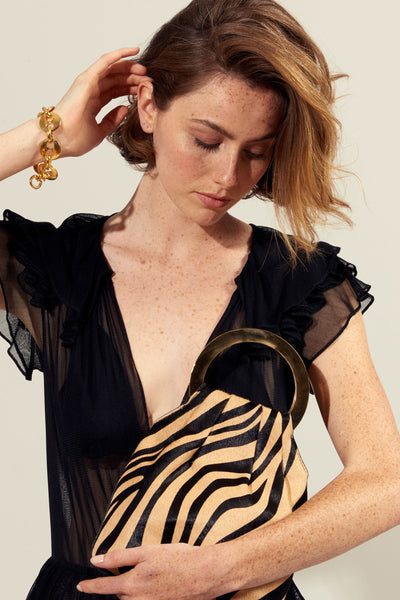 Thumbnail of Model holding the Alpine Bag In Zebra. Earn your style stripes with this graphic black and tan animal print calf-hair bag. It's roomy enough to hold your essentials yet sophisticated enough for a big night out. Lizzie's favorite feature? The very cool gold-plated round handles.