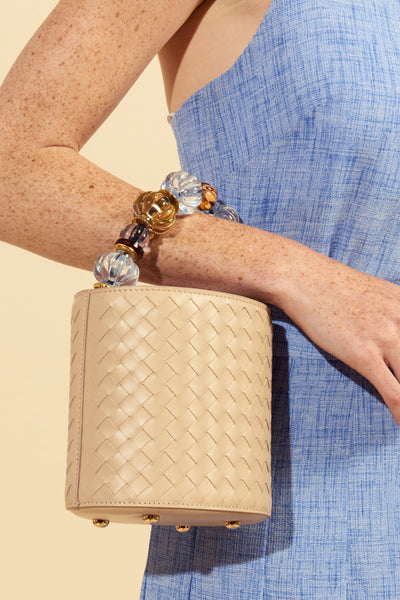 Thumbnail of model carrying the Florent Bag In Desert Mirage. Trust us, you are not seeing t...