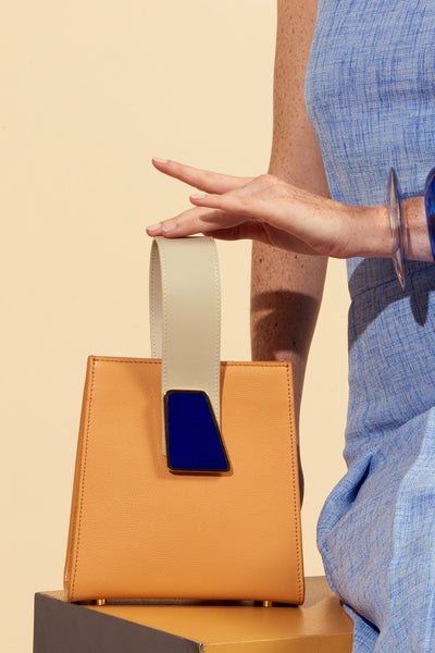 Thumbnail of model with Pronto Purse in Tangerine. Freshly squeezed? Yes, please. Our latest structured mini bag comes in gorgeous tangerine-colored textured leather, and features a beige leather top handle, abstract deep blue pebbled glass detail, and detachable leather cross-body strap.