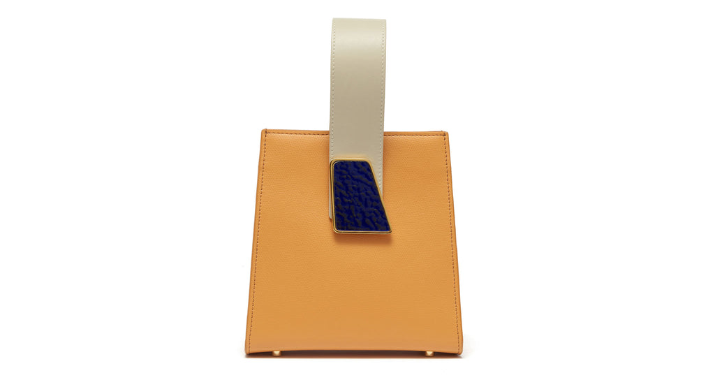 Full view of Pronto Purse in Tangerine. Freshly squeezed? Yes, please. Our latest structured mini bag comes in gorgeous tangerine-colored textured leather, and features a beige leather top handle, abstract deep blue pebbled glass detail, and detachable leather cross-body strap.