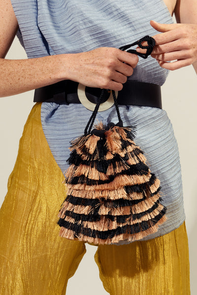 Thumbnail of model holding the Gala Wristlet In Zebra Fringe. Let's get wild! Bring out your inner party animal with our drawstring mini bag, with black & tan zebra-striped fringe and black twist cord wristlet.