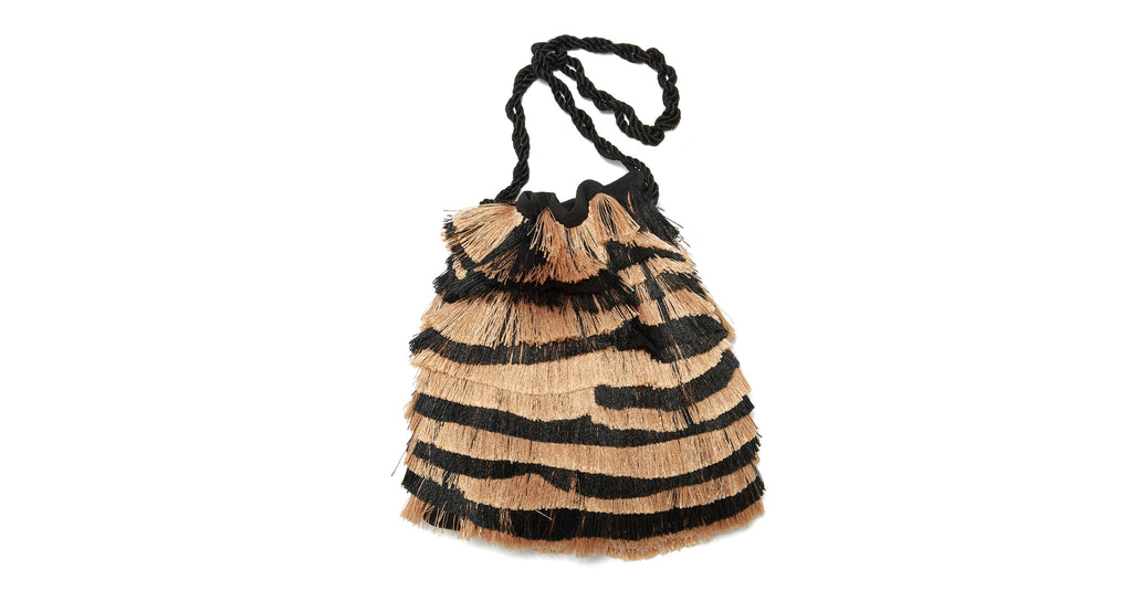 Full view of Gala Wristlet In Zebra Fringe. Let's get wild! Bring out your inner party animal with our drawstring mini bag, with black & tan zebra-striped fringe and black twist cord wristlet.