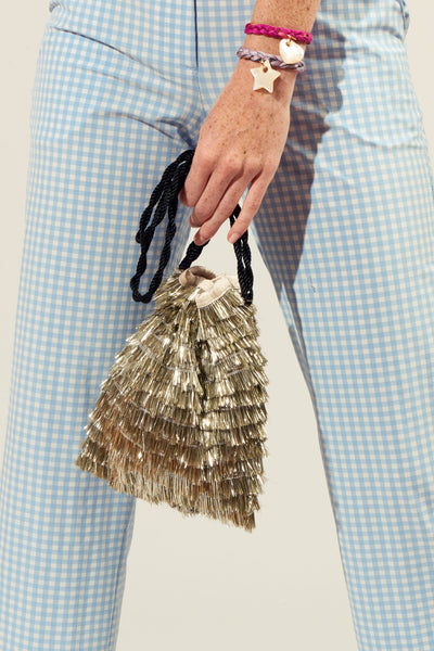 Thumbnail of model carrying the Gala Wristlet In Stardust. What are you doing New Year's Eve? Tote the drawstring purse of your party dreams, wherever the night may take you. With swingy metallic silver fringe and black twist cord wristlet.