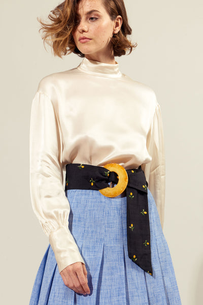 Thumbnail of model wearing Brigitte Belt In Orange Blossom. We've brought back Brigitte, our statement obi belt that lends both softness and structure to any outfit. In black silk shantung with a pretty embroidered flower motif and marbled apricot-colored acrylic buckle closure.