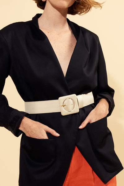 Thumbnail of model wearing the Agnes Belt In Cream Silk. Our favorite wide belt silhouette got a makeover in dreamy cream-coloured silk. With signature oversized square buckle.