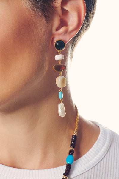 Thumbnail of model in the Heroine Earrings. Save the day in this amazing pair of asymmetrica...