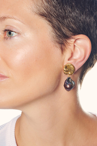 Thumbnail of model in the Coin Reflection Earrings in Peacock. For those who like it darker,...