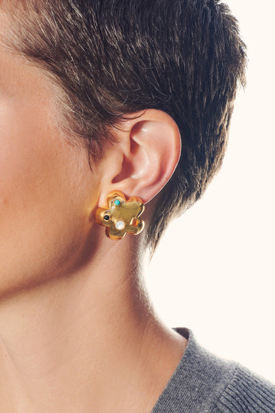 Thumbnail of model in the Gold Daisy Stud Earrings. Infuse your look with a little flower po...