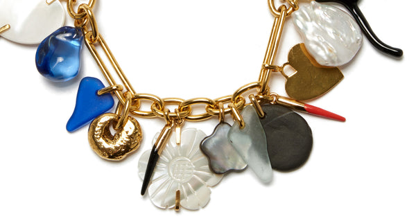 Bottom detail of Treasure Chest Charm Bracelet. This heirloom-worthy chain-link bracelet is a veritable treasure trove of style. Its charms include an eclectic mix of hearts, shaped coral branches, sea glass, flowers, and more.