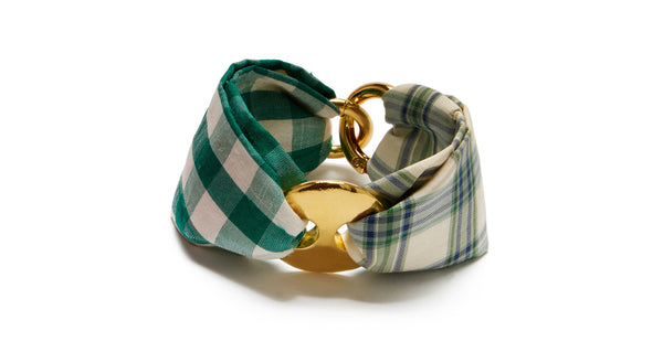 Full view of Jane Bracelet In Green Plaid. Bring a little softness to your stack with the green plaid & gingham two-tone silk fabric bracelet. Gold-plated cinch and clasp hardware anchors the easy new silhouette that we can't wait to wear with everything.