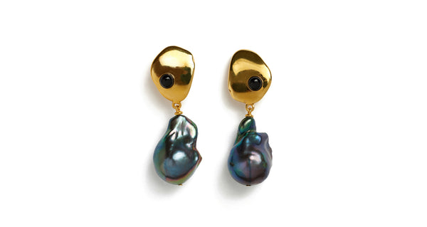 Full view of Black Sand Earrings. This season's most elegant little pair of earrings is here. Abstract gold-plated earrings are inset with onyx cabochons and capped off with the unique iridescence of baroque peacock pearls.
