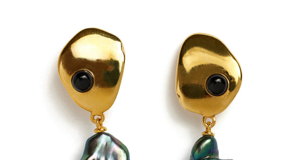 Top detail of Black Sand Earrings. This season's most elegant little pair of earrings is here. Abstract gold-plated earrings are inset with onyx cabochons and capped off with the unique iridescence of baroque peacock pearls.